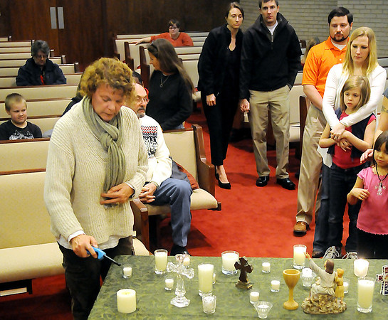 Worshipers light candles during a vigil at Central Christian Church for the victims in the Newtown, CT school shooting. (Staff Photo by BILLY HEFTON)