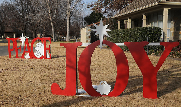 Peace and Joy decorations adorn the front landscape at 2421 Rockwood Thursday. Christmas spirit abounds throughout Enid as residents decorate their homes and landscapes for the holidays. (Staff Photo by BONNIE VCULEK)