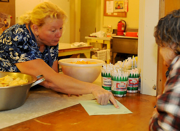 Jackie Egelston (left) assists a guest with a Christmas list Monday during a Mamre meal at University Place Christian Church. Egelston helps with the preparation of the meal each week. (Staff Photo by BONNIE VCULEK)