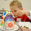 Richard Reisner concentrates as he decorates his gingerbread house during the March of Dimes Breakfast with Santa at Enid High School Saturday. (Staff Photo by BONNIE VCULEK)