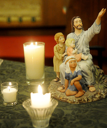 Candles burn next to a figurine during a vigil at Central Christian Church for the victims in the Newtown, CT school shooting. (Staff Photo by BILLY HEFTON)