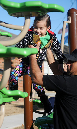 Mario Lupercio lifts his daughter, Ximena, onto a Champlin Park Playground obstacle Saturday, Dec. 28, 2013. Lupercio, his wife Mari, and their children Ximena, Camila and Mateo enjoyed the afternoon in the warm sun as temperatures climbed into the lower 60s. (Staff Photo by BONNIE VCULEK)