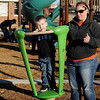 Harvick Sowers (left), from Garden City, Kan., balances inside a spinning toy at Champlin Park Playground as his Aunt Sally watches Saturday, Dec. 28, 2013. Families spent the day at the city parks as temperatures reached the lower 60s. (Staff Photo by BONNIE VCULEK)