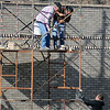 Masonry specialists drop a bucket to a fellow worker as they brick the exterior of Galaxy Mattress, 530 S. Van Buren, Saturday, Dec. 28, 2013. The City of Enid issued more building permits during the past year as business and residential construction increased. (Staff Photo by BONNIE VCULEK)