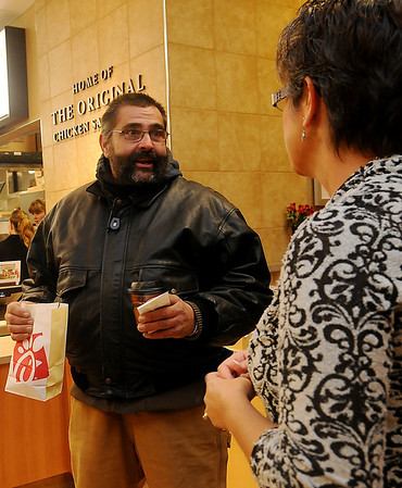 Ronn Lewis, from Oklahoma City, holds the first-ever breakfast order at the new Chick-fil-A restaurant in Enid as he visits with owner, Connie Sturgeon-Hart, Thursday, Dec. 12, 2013. Lewis, a Chick-fil-A fanatic, has attended seven different restaurant openings. (Staff Photo by BONNIE VCULEK)