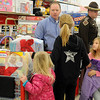 "Enid Police Capt. Bryan Skaggs visits with Belle, Jazmyn and Aeriel Koehn during ""Shop with a Cop"" inside the Big K Mart. The Enid Police Department and Oklahoma Highway Patrol Troop J provided Christmas gifts for sixty-five children in the Enid community. (Staff Photo by BONNIE VCULEK)"