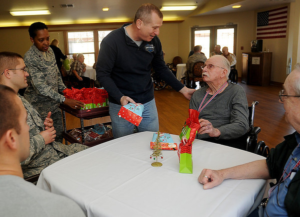 Retired Chief M.Sgt. Andrew Ridenhower (top, center), President of the Green Knights Military Motorcycle Club, with Vance Air Force Base Chaplain, Major Ruth Segres (back, left), presents gifts to Veterans at Greenbrier Saturday, Dec. 14, 2013. Each Veteran received a challenge coin and homemade cookies prepared by the Enid High School life skills class. (Staff Photo by BONNIE VCULEK)