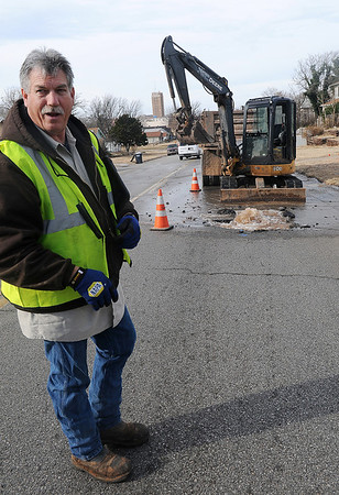 Water bubbles up from a main line break in the 600 block of E. Randolph as Mike Williams waits for additional City of Enid workers to arrive so the line can be repaired Thursday, Dec. 19, 2013. (Staff Photo by BONNIE VCULEK)