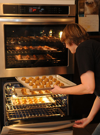 Joanne Crain fills her new convection oven with gingersnap and pumpkin-chocolate chip cookies as the family prepares more than 1800 cookies Saturday, Dec. 21, 2013. The double oven was installed Friday as Crain's early Christmas present, replacing a two-shelf single oven. (Staff Photo by BONNIE VCULEK)