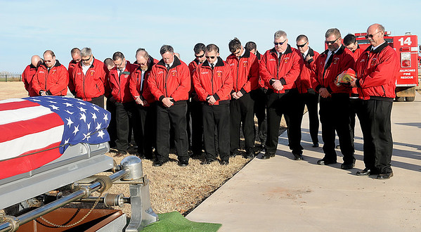 Waukomis Fire & Rescue bow their heads in prayer as they remember fellow firefighter Ronald Tuma during his interment ceremony at the Bison Cemetery. Tuma, who had served on the department for several years, lost his battle with cancer. (Staff Photo by BONNIE VCULEK)