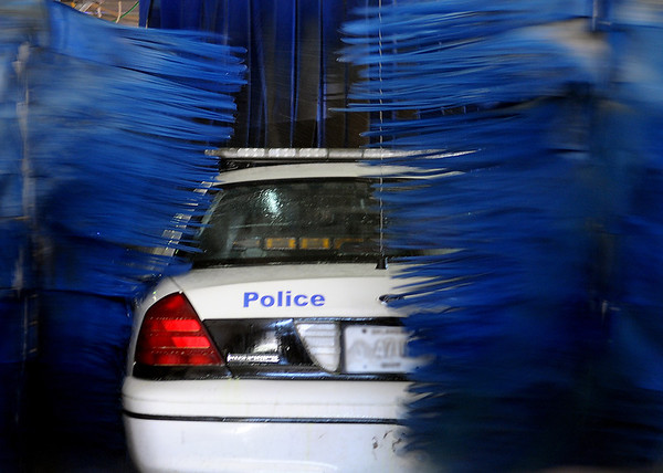 An Enid Police Department patrol car disappears between rotating brushes at Aqua Express Car Wash Saturday, Dec. 28, 2013. With warmer temperatures, drivers spent time washing their vehicles before Sunday's forecast high of 28 degrees. (Staff Photo by BONNIE VCULEK)