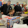 "Patrolman Dustin Fitzwater and Sgt. Dustin Albright assist children with their gift purchases during ""Shop With a Cop"" at the Big K Mart Saturday, Dec. 14, 2013. (Staff Photo by BONNIE VCULEK)"
