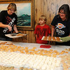 Gunner Olson (center) devours a peanut butter blossom cookie as Joanne Crain (left) and her sister-in-law, Dianne Olson (right), place warm pumpkin/semi-sweet chocolate chip cookies on a table filled with hundreds of sweet treats prepared by the family Saturday, Dec. 21, 2013. The Christmas baking tradition began several generations ago. (Staff Photo by BONNIE VCULEK)