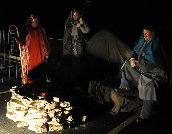 Shepherds warm themselves by a fire during the Enid First Nazarene Church living drive-through nativity Friday, Dec. 13, 2013. Members of the congregation portray Biblical characters during the living nativity 6:30-9 p.m. through Sunday. (Staff Photo by BONNIE VCULEK)