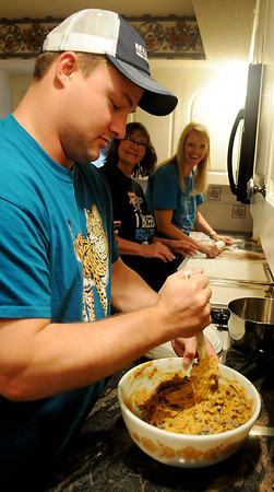 Spencer Olson stirs pumpkin, semi-sweet chocolate chip cookie dough during the Crain and Olson traditional Christmas baking day Saturday, Dec. 21, 2013. More than 1800 cookies, 13 different kinds, are prepared during the day. (Staff Photo by BONNIE VCULEK)