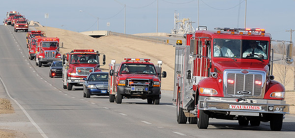 Waukomis Fire & Rescue apparatus trucks escort the remains of volunteer firefighter, Ronald Tuma, from St. Gregory the Great Catholic Church to his final resting place at the Bison Cemetery Wednesday, Dec. 18, 2013. (Staff Photo by BONNIE VCULEK)