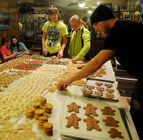 Family members stack cooled, homemade cookies so warm gingerbread men can be removed from cookie sheets Saturday, Dec. 21, 2013. The Crain and Olson families gather each year at Christmas to carry on the cookie baking tradition. (Staff Photo by BONNIE VCULEK)