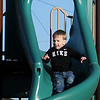 Harvick Sowers, from Garden City, Kan., slides at the new Champlin Park Playground Saturday, Dec. 28, 2013. (Staff Photo by BONNIE VCULEK)