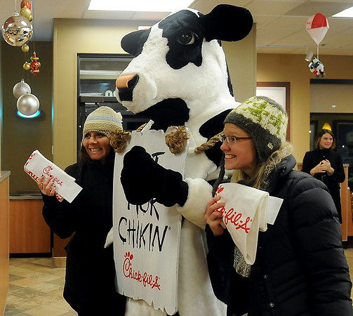 Campers pause for a portrait with the Chick-fil-A cow after they received chicken nuggets, a t-shirt and their gift certificates for free food for a year during the grand opening at 6 a.m. Thursday, Dec. 12, 2013. Connie Sturgeon-Hart and her husband Steve opened their franchise inside Oakwood Mall 26 years ago, and re-opened their restaurant near the mall at 4329 W. Owen K. Garriott. (Staff Photo by BONNIE VCULEK)