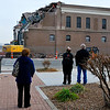 Interested people watch as a tract hoe continues the demolition of the Kress Building Sunday. (Staff Photo by BILLY HEFTON)