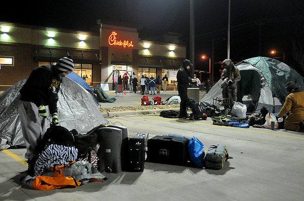 Enthusiastic campers line up for their free food certificates (back center) as others pack up their belongings outside the newest Chick-fil-A restaurant in Enid Thursday, Dec. 12, 2013. (Staff Photo by BONNIE VCULEK)