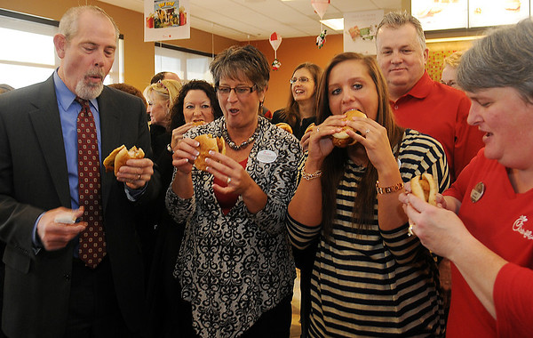 Jon Blankenship, Connie Sturgeon-Hart, her daughter Erica and Steve Hart (front, from left) enjoy a Chick-fil-A sandwich during the grand opening ribbon cutting at the new Enid restaurant Thursday, Dec. 12, 2013. Connie Sturgeon-Hart and her husband, Steve, opened a franchise in Oakwood Mall 26 years ago until the new location was purchased near the mall and built at 4329 W. Owen K. Garriott. (Staff Photo by BONNIE VCULEK)