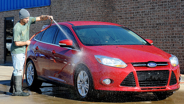 An Aqua Express Car Wash attendant cleans the exterior of a vehicle in the free car wash line Saturday, Dec. 28, 2013. With warmer temperatures, drivers waited in long lines to wash the grime from their automobiles before Sunday's freezing temperatures arrive. (Staff Photo by BONNIE VCULEK)