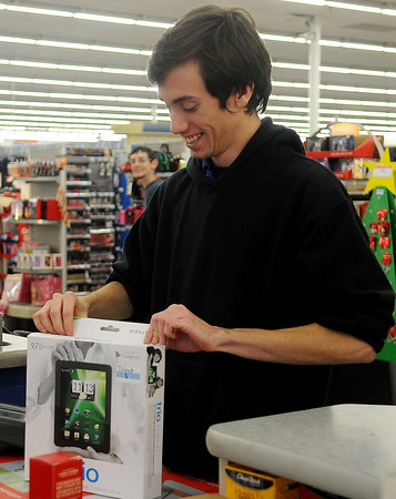 Dakota Vasquez smiles as he picks up electronic returns for his department at the Big Kmart Thursday, Dec. 26, 2013. Shoppers lined up early in the morning to exchange their items, but by mid-afternoon the return lines were much shorter. (Staff Photo by BONNIE VCULEK)