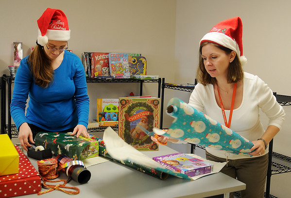 Shawna Lounsbury (left), a YWCA Reflections Halfway House employee, and Marjorie Haskin, a military spouse who volunteers at the YWCA Crisis Center, wrap gifts inside the Elf Room at the YWCA Wednesday, Dec. 4, 2013. Parents, who have been in a crisis situation that reside at the YWCA, select gifts from the Elf Room for their children. Donations for newborn children through teens are still needed for this Christmas. (Staff Photo by BONNIE VCULEK)