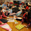 Enid High School Pacers' basketball team wraps Christmas presents for a family with four chlldren Thursday, Dec. 19, 2013. With the help of Peggy Kenega, Taft Elementary School principal, a Christmas wish list from each child was prepared for the players. Grace Enmeier (front, right) organized the information and every one on the team and their coaches purchased items from the lists. Players will deliver the gifts early Monday morning. (Staff Photo by BONNIE VCULEK)