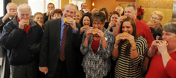 Chick-fil-A enthusiasts join Connie Sturgeon-Hart, friends and family in a first bite of a chicken sandwich during the grand opening of the restaurant Thursday, Dec. 12, 2013. Sturgeon-Hart and her husband, Steve Hart, opened their first Chick-fil-A franchise inside Oakwood Mall 26 years ago until the new free-standing restaurant could be opened. (Staff Photo by BONNIE VCULEK)