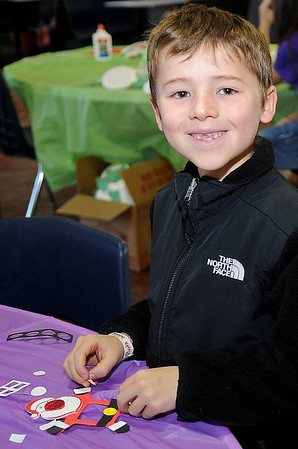 Dawson Branstetter smiles as he creates a Santa Christmas frame during the 15th annual March of Dimes Breakfast with Santa at Enid High School Saturday, Dec. 7, 2013. (Staff Photo by BONNIE VCULEK)
