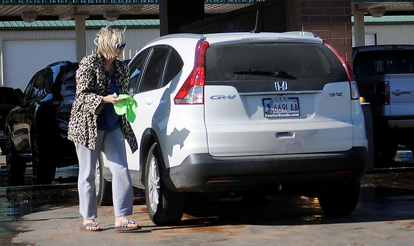 Pattie Adams waits in line to wash her new Honda CR-V Saturday, Dec. 28, 2013. With warmer temperatures, drivers lined up at car washes across Enid before Sunday's expected high of 28 degrees. (Staff Photo by BONNIE VCULEK)