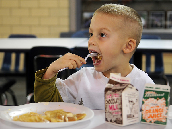 Henson Reames, 4, devours pancakes and sausage during the 15th annual March of Dimes Breakfast with Santa at Enid High School Saturday, Dec. 7, 2013. (Staff Photo by BONNIE VCULEK)