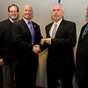 Enid Police Department Chief Brian O'Rourke (second, from right) accepts the key to a new narcotics vehicle from Darrell Weaver (third, from left), the Director of the Oklahoma Bureau of Narcotics, in the EPD classroom Tuesday, Dec. 3, 2013. Bob Cook (far left), narcotics division director of OBN, Sen. Patrick Anderson (second, from left) and EPD Capt. Kevin Morris (far right) were also present during the transfer of ownership. (Staff Photo by BONNIE VCULEK)