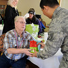 Navy Veteran Frank Hite, a third class Water Tender aboard the USS Bagley, receives Christmas gifts from S.Sgt. Kevin Phone during the Vance Air Force Base chapter of the Green Knights Military Motorcycle Club veteran visit at Greenbrier Saturday, Dec. 14, 2013. Each veteran was given a challenge coin and homemade cookies prepared by the Enid High School life skills class. (Staff Photo by BONNIE VCULEK)