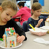 Kate Curran and her older sister, Grace, create their gingerbread houses during the 15th annual March of Dimes Breakfast with Santa at Enid High School Saturday, Dec. 7, 2013. (Staff Photo by BONNIE VCULEK)