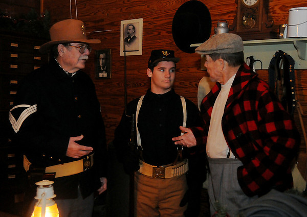 Quartermaster Sgt. Steve Wilson, Private Elijah Green and U.S. Land Office clerk David Clark (from left) discuss the duties of the 13th Infantry C Company as they guarded the land office in Humphrey Heritage Village during Christmas in the Village at the Cherokee Strip Regional Heritage Center Friday, Dec. 6, 2013. (Staff Photo by BONNIE VCULEK)