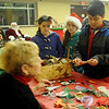 As Santa watches (back left), children make traditional Christmas ornaments out of paper cones and lace during Christmas in the Village at the Cherokee Strip Regional Heritage Center Friday, Dec. 6, 2013. (Staff Photo by BONNIE VCULEK)