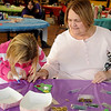 Katelyn Reames and her grandmother, Linda, work on a Christmas tree ornament during the 15th annual March of Dimes Breakfast with Santa at Enid High School Saturday, Dec. 7, 2013. (Staff Photo by BONNIE VCULEK)
