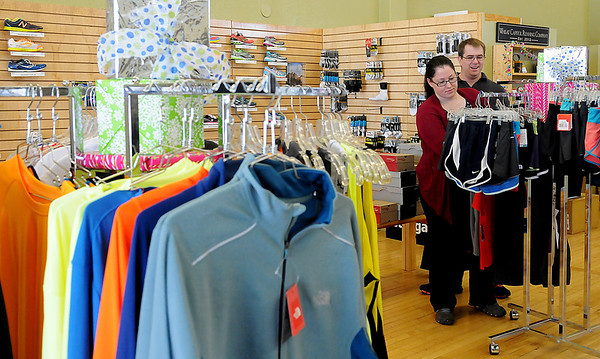 Melissa and Shawn Szymanski shop at Wheat Capital Running Company Wednesday, Dec. 13, 2013. The downtown Enid business is closing after two years. (Staff Photo by BONNIE VCULEK)