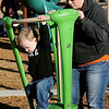 Harvick Sowers, from Garden City, Kan., leaps off a toy as his Aunt Sally holds it during playtime at Champlin Park Saturday, Dec. 28, 2013. Temperatures reached the lower 60s Saturday afternoon, before dropping to the 20s Sunday. (Staff Photo by BONNIE VCULEK)