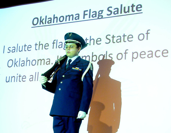 An Enid High School ROTC cadet stands near the words of the Oklahoma Flag Salute during the Waller Day assembly at Waller Middle School Friday, Dec. 6, 2013. (Staff Photo by BONNIE VCULEK)