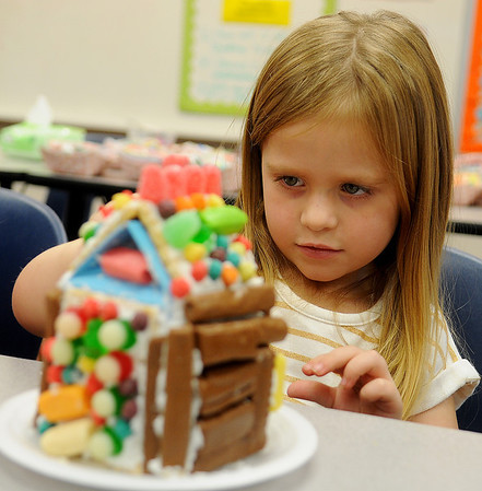 Austynn Puckett decorates her gingerbread house during the 15th annual March of Dimes Breakfast with Santa at Enid High School Saturday, Dec. 7, 2013. (Staff Photo by BONNIE VCULEK)