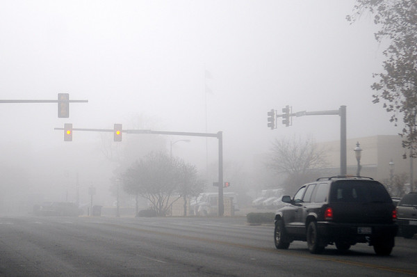 Drivers travel with caution as dense fog limited visibility in downtown Enid and across Garfield County Tuesday, Dec. 3, 2013. (Staff Photo by BONNIE VCULEK)