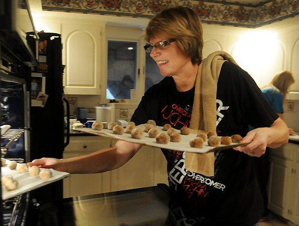 Joanne Crain places gingersnap cookies into her new convection oven to bake as the Crain and Olson families prepare more than 1800 cookies for friends and family members Saturday, Dec. 21, 2013. The double oven was installed Friday as Crain's early Christmas present, replacing a two-shelf single oven. (Staff Photo by BONNIE VCULEK)