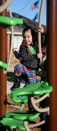 Ximena Lupercio, daughter of Mario and Mari Lupercio, uses both hands as she climbs a giant leaf obstacle at the new Champlin Park Playground Saturday, Dec. 28, 2013. Families spent the day at the city parks as temperatures reached the lower 60s. (Staff Photo by BONNIE VCULEK)