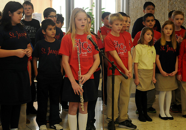 Cate Cunningham sings a solo as the St. Joseph Catholic School 3rd-5th grade students entertain the guests with a medley of Christmas carols at Central National Bank Friday, Dec. 6, 2013. (Staff Photo by BONNIE VCULEK)
