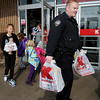 An Enid Police Officer helps Mary Koehn's children carry their Christmas gifts as they leave KMart Saturday, Dec. 14, 2013. Sixty-five children were allowed spend $100 each during the event sponsored by the Enid Police Department and the Oklahoma Highway Patrol Troop J. (Staff Photo by BONNIE VCULEK)