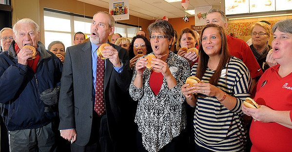 "Enid Chamber of Commerce ambassadors join Connie Sturgeon-Hart, Steve Hart, their daughter Erica and the Chick-fil-A staff in a rousing ""Eat Mor Chikin"" during the grand opening of the newest Chick-fil-A restaurant at 4329 W. Owen K. Garriott Thursday, Dec. 12, 2013. (Staff Photo by BONNIE VCULEK)"